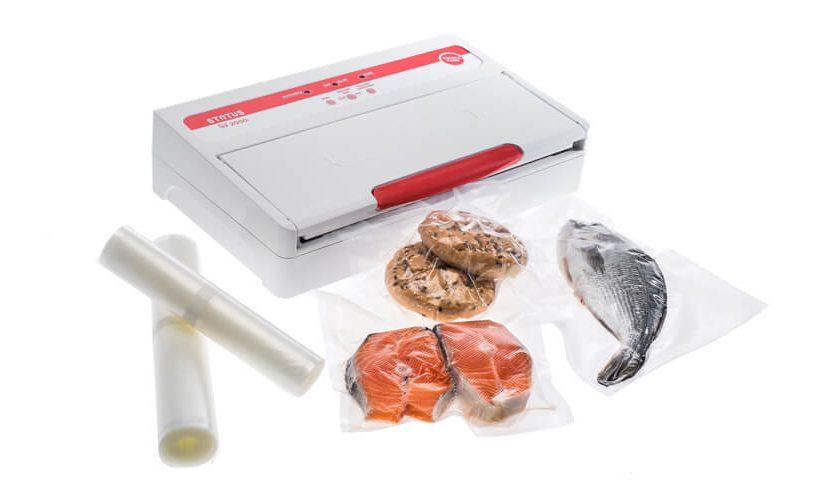 Vakuumski aparat SV2000 z zavakuumiranim lososom, žemljami in ribo na beli podlagi.