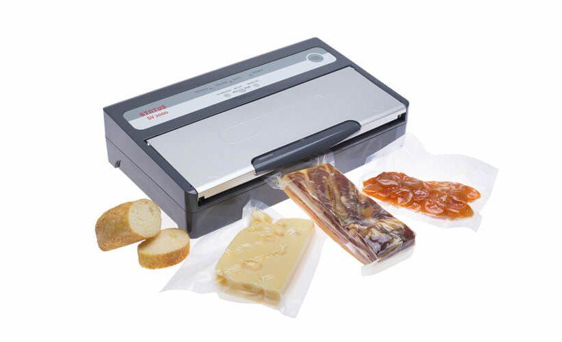 Srebrno-siv aparat za vakuumiranje SV2000 z zavakuumirano slanino in sirom.
