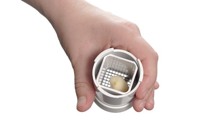 Odprt rezalnik česna, v katerega je vstavljen en strok česna.