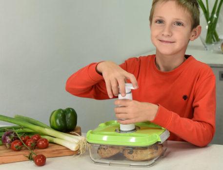 Deček v kuhinji vakuumira vakuumsko posodo z ročno vakuumsko črpalko.