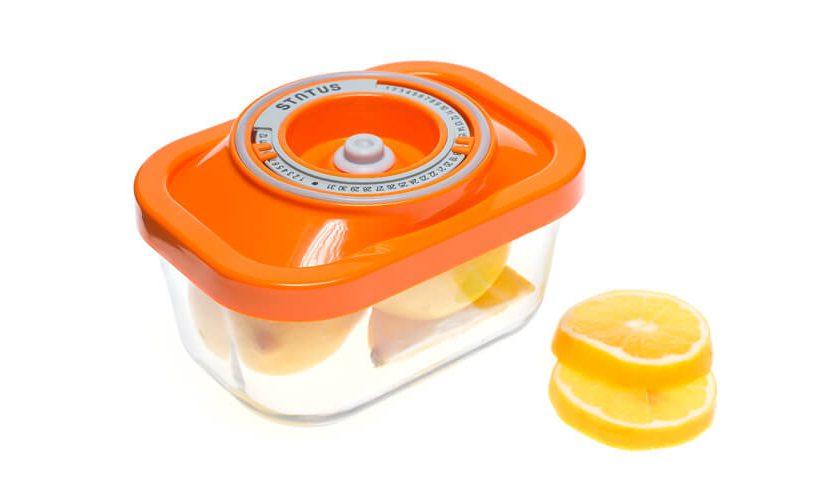 Najmanjša steklena vakuumska posoda z oranžnim pokrovom, v kateri je shranjena narezana limona.