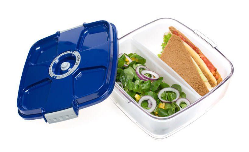 Kvadratna vakuumska posoda z modrim pokrovom in vložnimi posodicami, v katerih sta shranjena sendvič in solata.