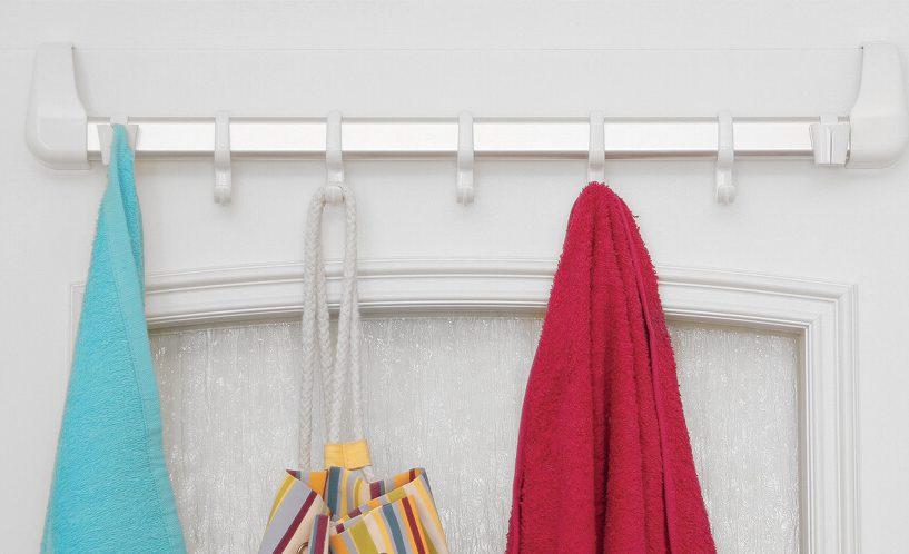 Obešalnik za na vrata Status v beli različici zataknjen na vratih, na njem visijo oblačila.