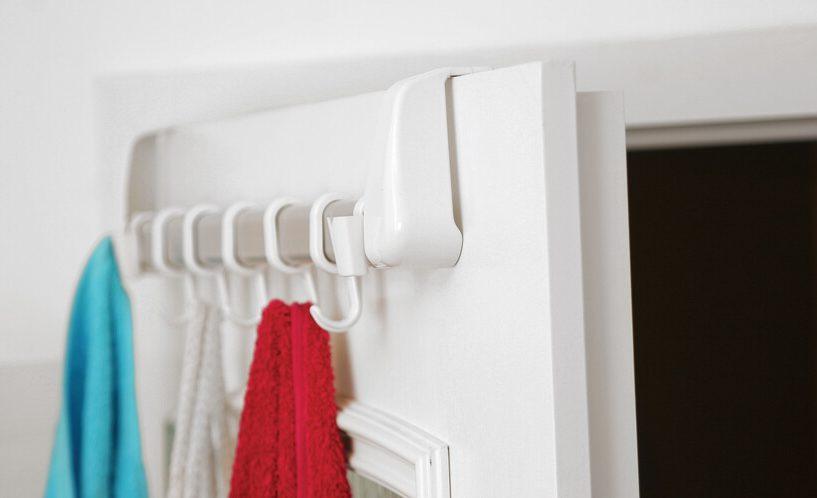 Beli obešalnik na priprtih vratih - prikaz od blizu.