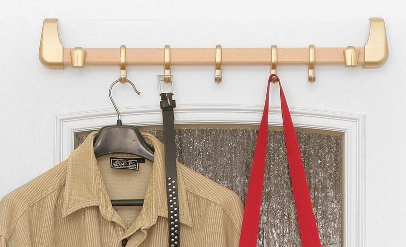 Zlati obešalnik nature line na belih vratih, na katerega je obešena torbica, pas in srajca.