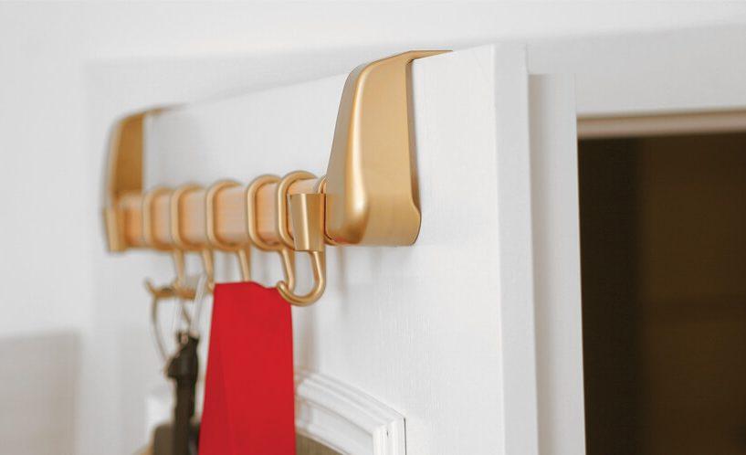 Prikaz zlatega obešalnika zataknjenega na vrata.