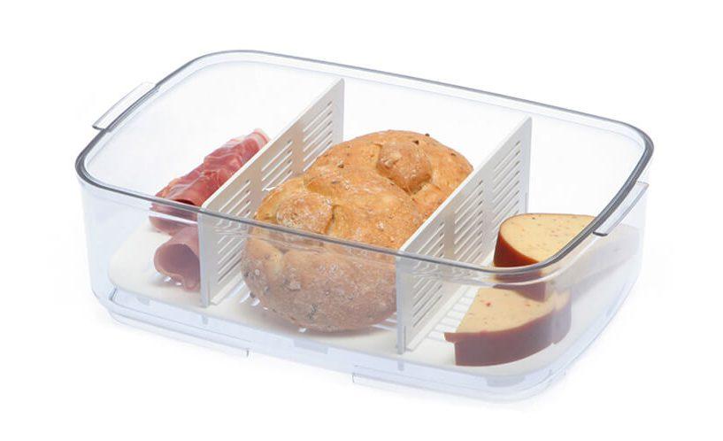Odcejalnik s pregradama v odprti posodi, salama, sir in štručka kruha.