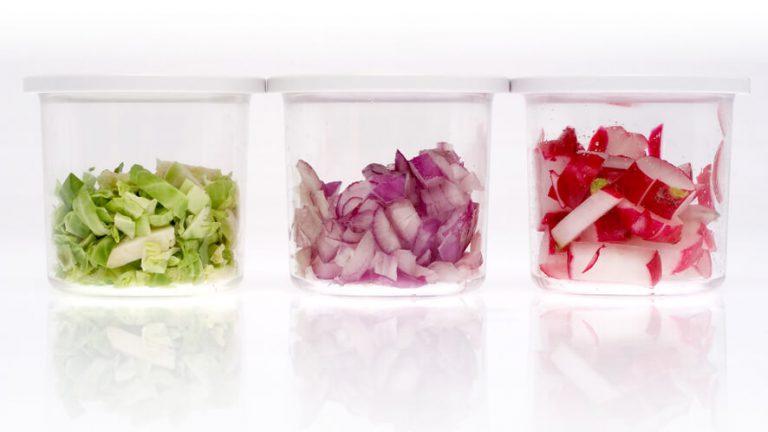 Narezana živila v zbiralni posodici mini rezalnika čebule.