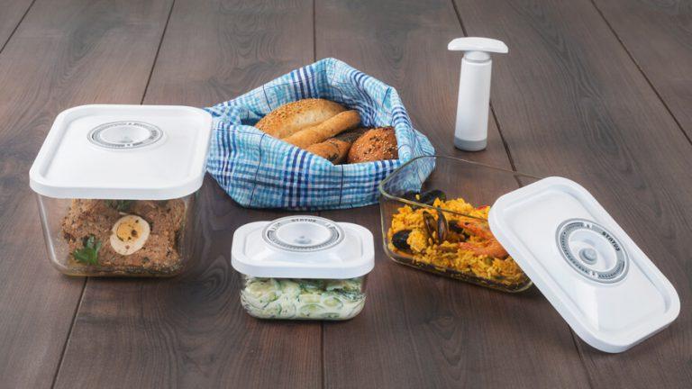4-delni set steklenih vakuumskih posod z živili na rjavih deskah.