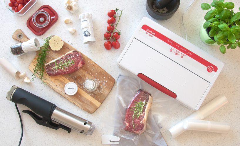 Počasni kuhalnik, vakuumski aparat z zavakuumiranim mesom, deska za rezanje in meso, paradižnik na belem pultu.