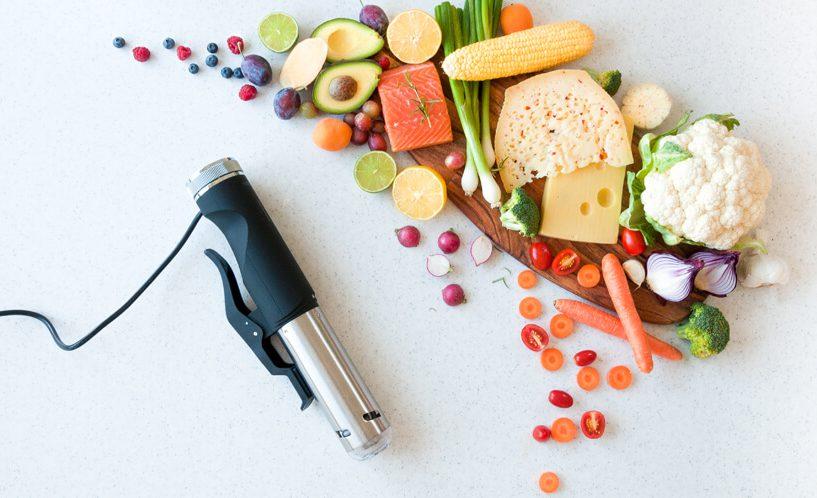 Ležeči Sous Vide kuhalnik SVC100 in različna zelenjava desno.