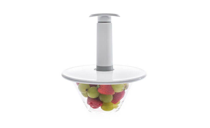 Ročna vakuumska črpalka na univerzalnem vakuumskem pokrov na skledi z grozdjem in jagodami