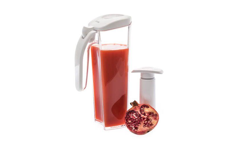 Beli vakuumski vrč Status s sokom granatnega jabolka in ročno vakuumsko črpalko..