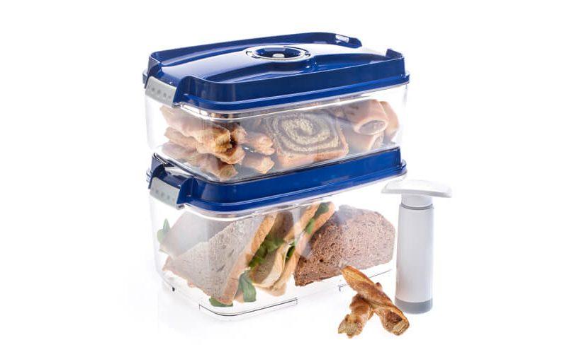 Vakuumski posodi z modrimi pokrovi, v katerih so shranjeni sendviči in pecivo. Ročna vakuumska črpalka.