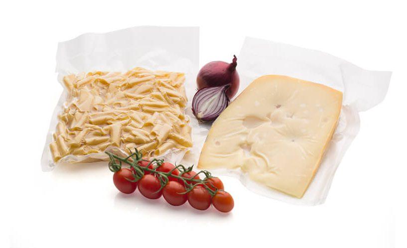 Vakuumsko shranjeni sir in fuži na belem ozadju.