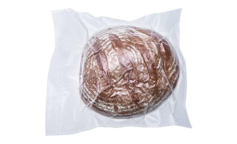 Zavakuumiran hlebec kruha v XL vrečki na belem ozadju.