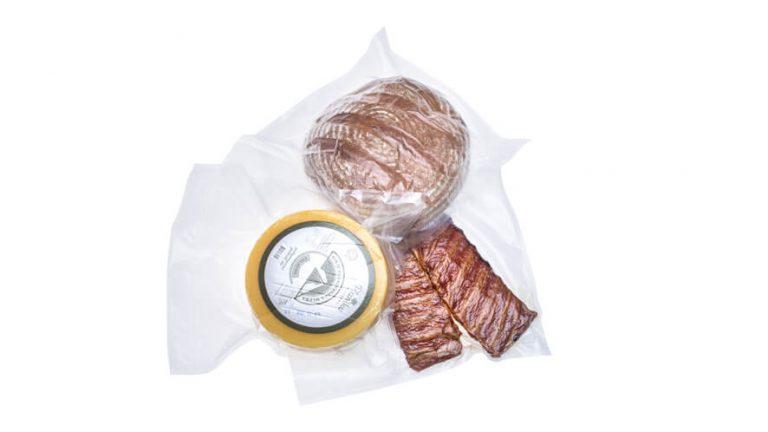 Zavakuumiran hlebec kruha, kolut sira in rebra v kosu na belem ozadju.