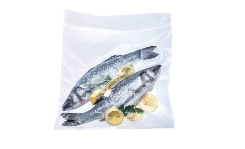 Zavakuumirani ribi z limono v XL vakuumski vrečki na belem ozadju.