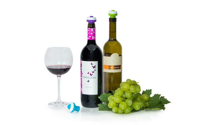 Steklenici vina z vakuumskimi zamaški, natočen kozarec črnine in grozdje na belem ozadju.