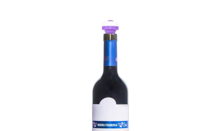 Vijolični vakuumski zamašek na steklenici vina na belem ozadju.